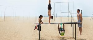 Група спортуващи млади хора с ластици на площадка за фитнес на плажа