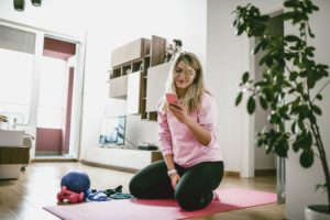Жена гледа тренировка от телефона си върху постелка за упражнения вкъщи